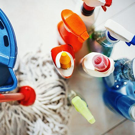 Closeup top view of unrecognizable home cleaning products with blue bucket and a mop on the side. All products placed on white tiled bathroom floor.